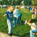 Two girls are playing on a log that will be used in the railsplitting competition.